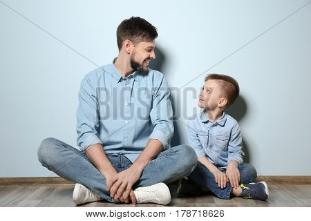 Father and his son sitting on floor near color wall