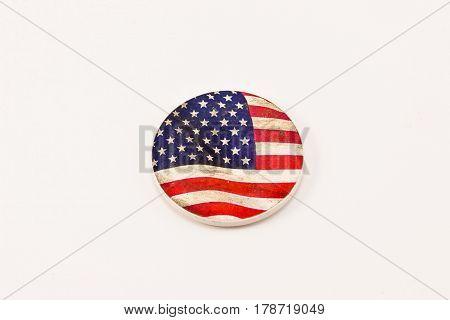 a small three inch round ceramic flag medallion