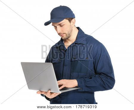 Handsome auto mechanic with laptop on white background