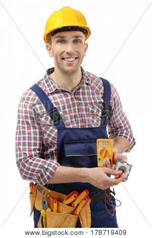 Young electrician holding socket and multimeter on white background