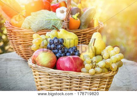 Autumn harvest - fresh organic fruit and vegetable in wicker basket on table
