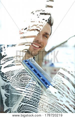 Young man washing window, view through glass