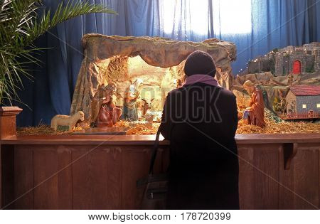 ZAGREB, CROATIA - DECEMBER 28: A woman prays in front of the Christmas creches in the Basilica of the Sacred Heart in Zagreb, on December 28, 2015.