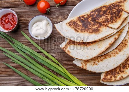 Tortillas with meat and onion , tomato on wooden table