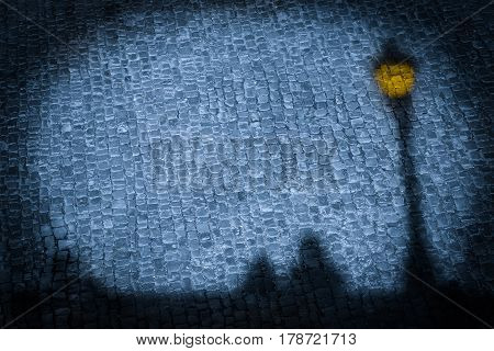 Shadow image nostalgic silhouettes of couple and illuminated lamppost in spotlight on cobblestone road background at night (copy space)