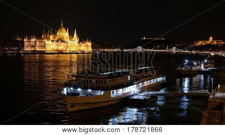 Night panorama of Budapest city centre with Parliament building, Chain Bridge, Buda Castle, Danube river and two boats