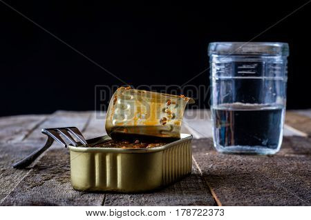 A glass of fish and bread on an old kitchen table
