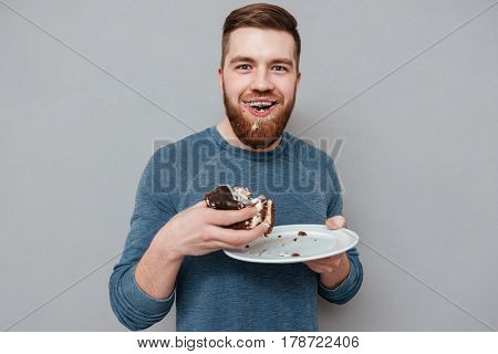 Filthy bearded young man eating chocolate cakes isolated on gray background