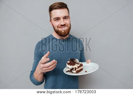 Happy smiling bearded man eating chocolate cake isolated on gray background