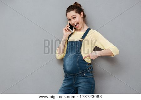 Portrait of a cheerful excited pregnant woman standing and talking on mobile phone isolated on a gray background