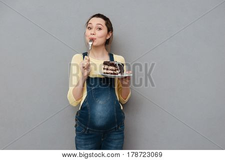 Portrait of a delighted young pregnant woman eating chocolate cake isolated on a gray background