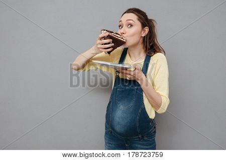 Portrait of a hungry happy pregnant woman eating sweet chocolate cake isolated on a gray background