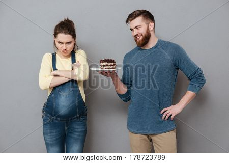 Smiling husband offers his unsatisfied pregnant wife a chocolate cake isolated