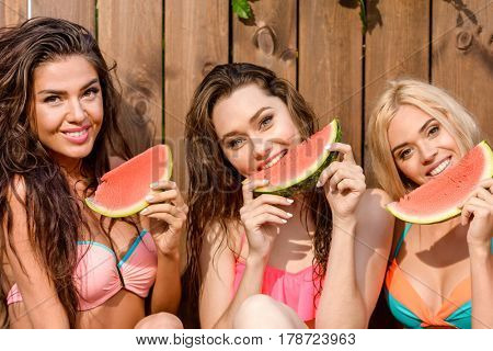 Three young cute funny girls eating watermelon over wooden background