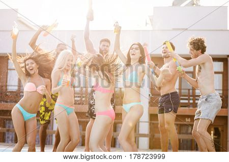 Group of best friends having party by swimming pool outdoors
