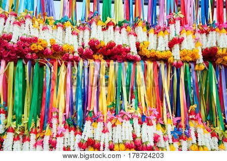 Colourful garlands hanging from a rack during a festival in Thailand.