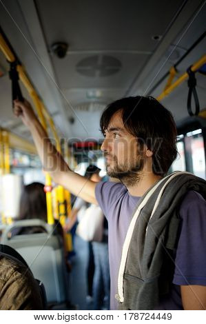 The young bearded man in the city bus. He stands in the aisle and holds a hand-rail. The man has a thoughtful look.