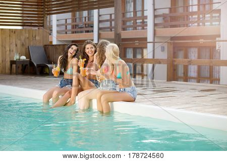 Happy cute young women with cocktails laughing and having fun near swimming pool