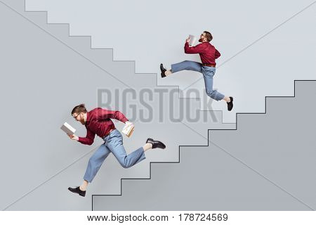 Two funny bearded twin men with books running up and down along drawn stairs on concrete wall