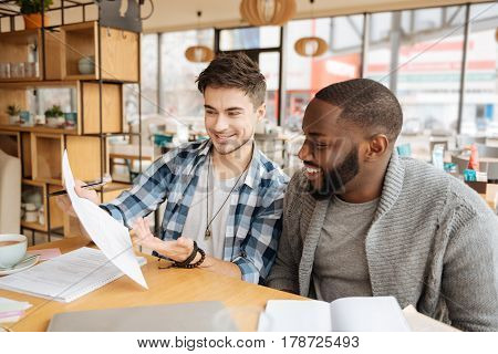Great idea. Young handsome guy is presenting his notes to the international fellow student while studying process at cafeteria.