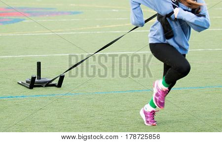 A teenager working out on a turf field while pulling a weighted sled for resistance training.