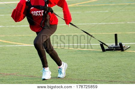 A girl running while pulling a weighted sled on a green turf field