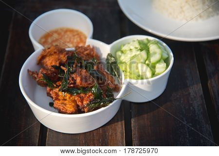 fried fish and cucumber with sauce and rice.