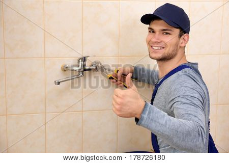 Handsome plumber fixing faucet in bathroom