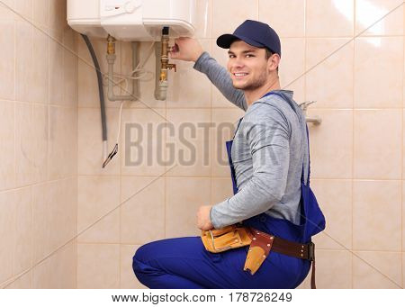 Young handsome plumber repairing boiler in bathroom