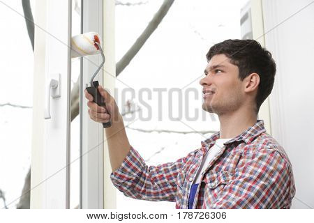 Young man painting window in office
