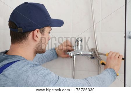 Plumber fixing faucet in shower stall