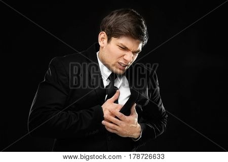 Heart attack concept. Young man suffering from chest pain on black background