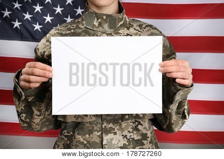 Female soldier with blank poster on flag background, closeup