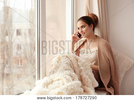 Beautiful young woman talking by mobile phone while sitting on window sill at home