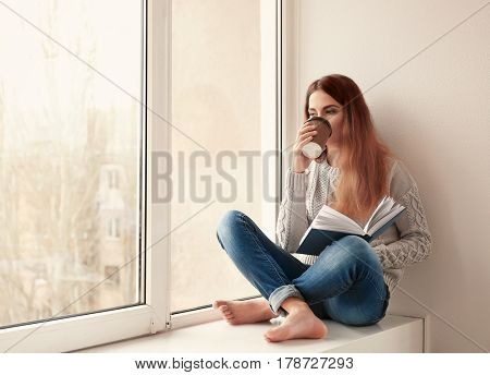 Beautiful young woman drinking coffee and reading book while sitting on window sill at home