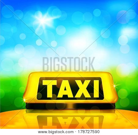Yellow taxi sign on the car on a blue sky background and green grass