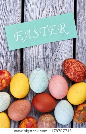 Dyed eggs and Easter card. Chicken eggs, gray wood background. Fun Easter facts.