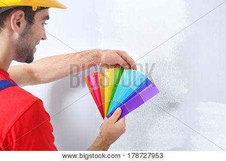 Worker holding palette for choosing color of wall