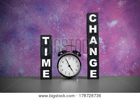 Cubes with text TIME CHANGE and retro alarm clock on table against color wall