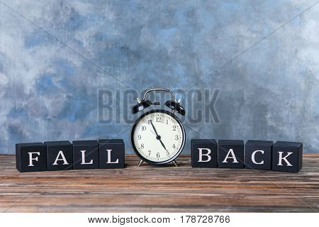 Cubes with text FALL BACK and retro alarm clock on table against color wall