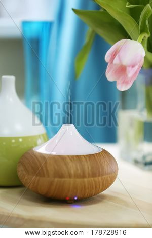 Aroma oil diffusers and flowers on table