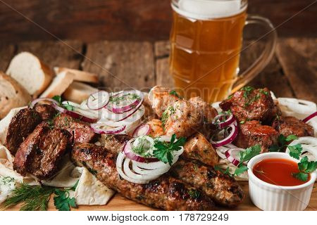 Appetizing meal in pub with fresh grilled meat assortment, pita bread, buns, and mug of cold light beer served on wooden table, close up view.