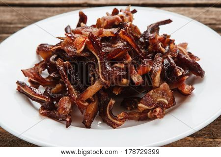 Unhealthy eating habits, junk food. Smoked pig ears served on white plate, close up view. Appetizing beer snack