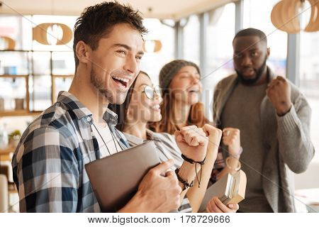 Extremely happy. Handsome youthful man is smiling and expressing happiness with his joyful fellows on background.