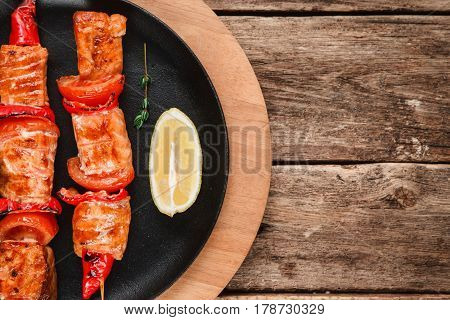 Roasted salmon with vegetables and lemon served on black plate, flat lay. Japanese restaurant menu photo with free space for text.