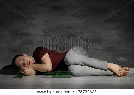 Handsome depressed man lying on floor with bottles at home