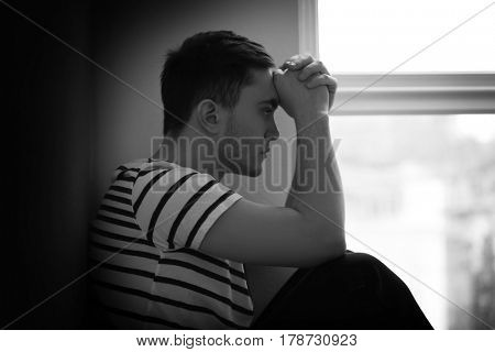 Handsome depressed man sitting by the window at home