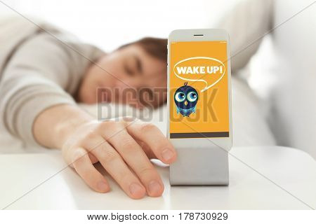 Young man going to switch off alarm clock signal on mobile phone while lying in bed at home