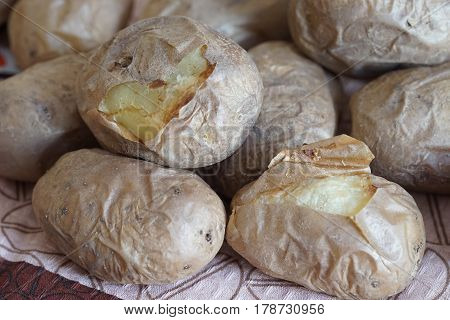 appetizing baked potatoes in peel lay on tablecloths