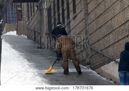 BRONX NEW YORK - MARCH 14: Man shovels street during snow storm. Taken March 14 2017 in New York.